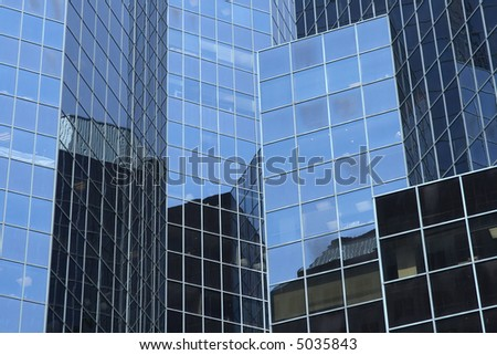Reflections in a modern glass-windowed office building.