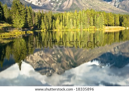 Reflections in Johnson lake in Banff - stock photo