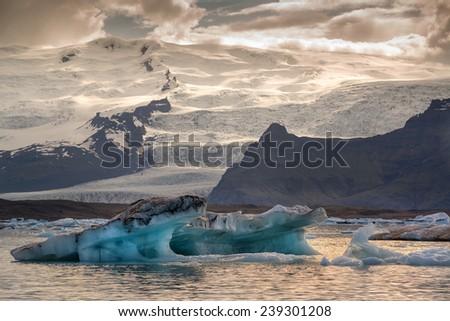 Reflections in Jokulsarlon lagoon in Iceland, by sunset - stock photo
