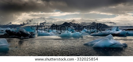Reflections in Jokulsarlon lagoon in Iceland, by sunset - stock photo