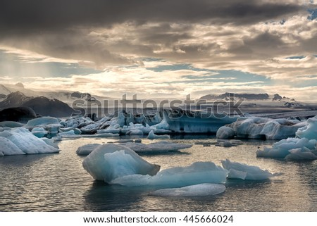 Reflections in Jokulsarlon lagoon in Iceland, by sunset