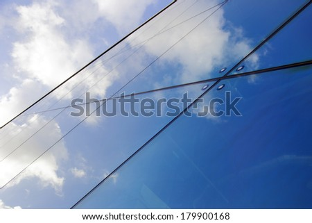 reflections of clouds and blue sky in modern glass facade - stock photo