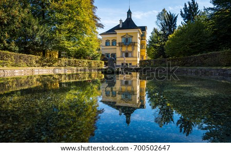 Reflections of Hellbrunn Palace surrounded by the beautiful water gardens in Salzburg, Austria.