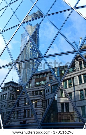 Reflections of more architecture in the Gherkin building London - stock photo