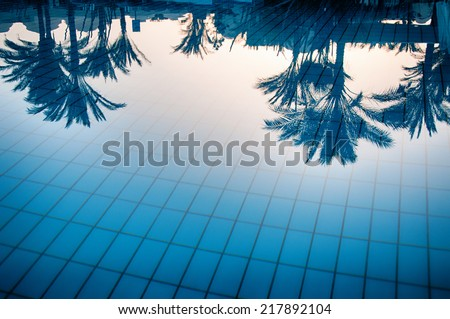 Reflections of palm trees in the calm blue water of a swimming pool conceptual of tropical summer vacations and travel - stock photo