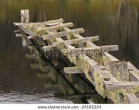 Reflections of the autumn colors. Mossy footbridge in the lake. - stock photo