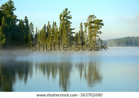 Reflections of the Coniferous Forest on a Foggy Wilderness Lake - stock photo