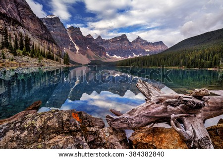 Reflections of the mountain range on the clear water, boulder and driftwood on the foreground - stock photo