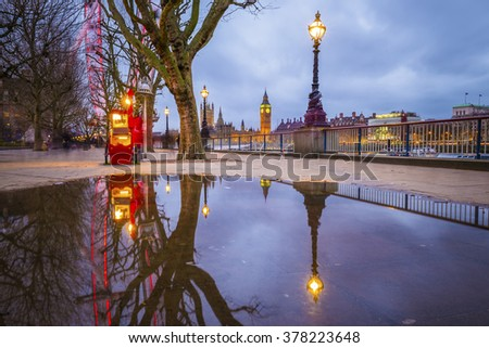 Reflections of the The Big Ben and Houses of Parliament taken from South Bank of River Thames at dawn with trees and cloudy sky - London, UK - stock photo