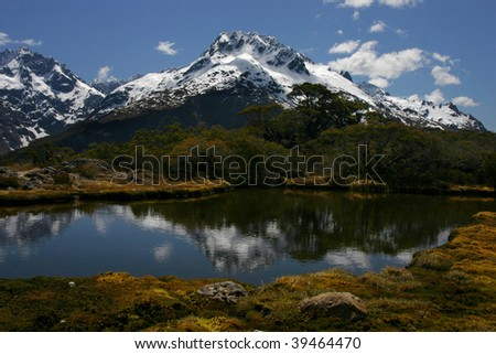 Reflections on Key Summit lake with snow on surrounding mountains