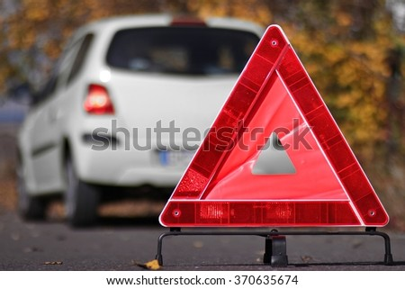 reflective triangle in front of a car breakdown - stock photo
