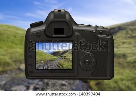 reflex digital camera on landscape background - stock photo