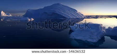 Reflexion of an iceberg after a sunset. Western Greenland. - stock photo
