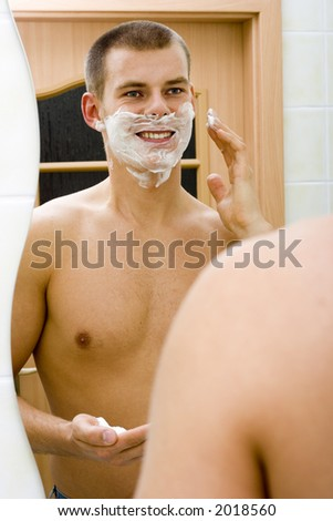 reflexion of young man in the bathroom's mirror with shave foam on face - stock photo