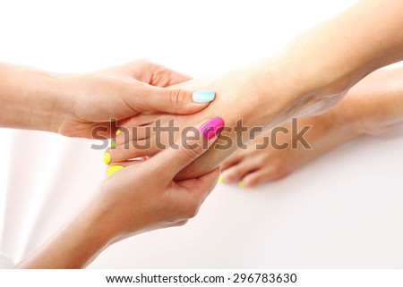 Reflexology foot massage.Beautician massaging woman's foot, acupressure treatment - stock photo
