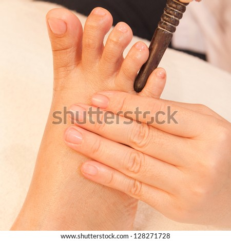 reflexology foot massage by stick wood, spa foot treatment,Thailand - stock photo