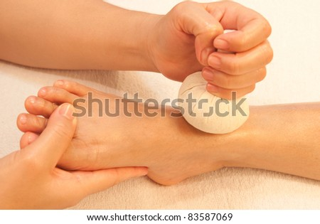 reflexology foot massage, spa foot treatment by ball herb,Thailand - stock photo