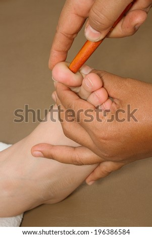 Reflexology foot massage, spa foot treatment by wood stick  in health center thailand - stock photo