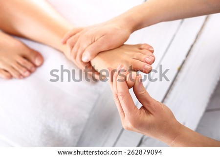 Reflexology.Woman in a beauty salon for pedicure and foot massage. - stock photo