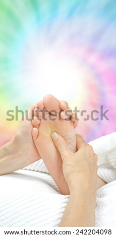 Reflexology working the Solar Plexus  -  Reflexologist holding a client's foot while applying pressure to the solar plexus area on a rainbow colored spiraling energy formation background - stock photo