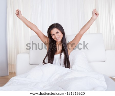 Refreshed young woman rejoicing in bed with her arms outstretched above her head rejuvenated by a good nights sleep - stock photo