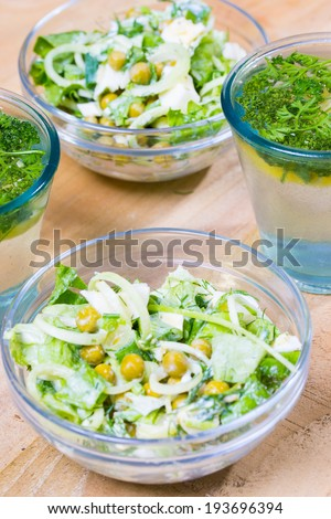 Refreshing and detoxing  lemonade with parsley and bowls of vegetarians healthy salad on the wooden table