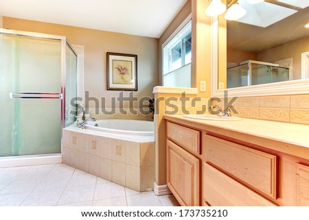 Refreshing bathroom with yellow and beige walls, tile floor, wood cabinets, glass shower and bath tub - stock photo