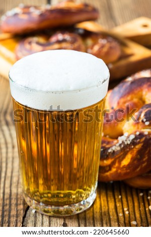 Refreshing beer ready to drink and fresh bavarian pretzels. Traditional food and drink for german Oktoberfest - stock photo