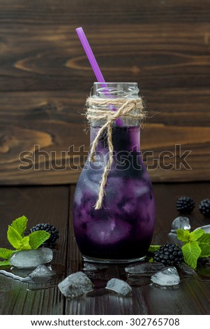 Refreshing blackberry juice in vintage eco style bottle on rustic dark wooden table. Cold summer berry drink with ice and mint. Clean eating - stock photo