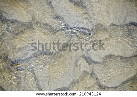 Refreshing blue tinted clear water shallow water creating ripples in the sand beneath  - stock photo