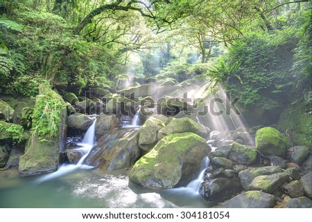 Refreshing cascades in a mysterious ravine of lush forest with sunlight shining through lavish greenery ~ Fascinating river scenery of Taiwan - stock photo
