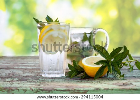 refreshing citrus lemonade,summer drink with mint and lemons on wooden plate, soft colored and focused green background  - stock photo