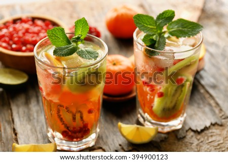 Refreshing cocktails with ice, mint, pomegranate seeds and slices of fruits on rustic wooden background