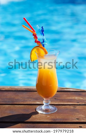 Refreshing coctail near swimming pool on vacation - stock photo