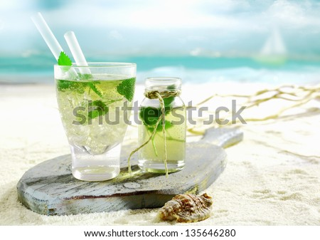 Refreshing cold Mojito cocktail with fresh mint served on an old wooden board lying on the golden sand of a tropical beach - stock photo