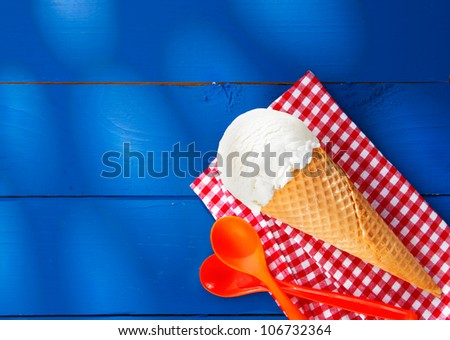 Refreshing creamy vanilla icecream cone served on a red and white checkered napkin lying on rustic blue wooden boards