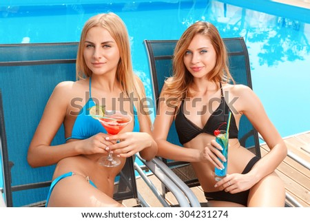 Refreshing drink. Two sexy girlfriends lying on chaise longue and holding freshly made cocktails. - stock photo