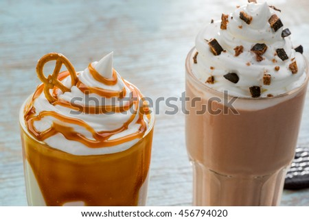 Refreshing drinks in the foreground of the camera. Delicious milkshakes are very popular nowadays in outdoor cafes. Different flavors of ingredients: vanilla, chocolate and caramel, salty cracknel. - stock photo