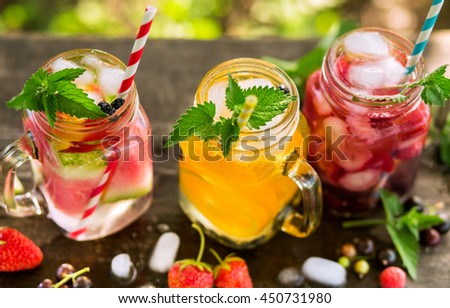 Refreshing drinks with ice in jars, orange juice, berry juice and watermelon water - stock photo