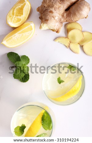 refreshing flavors of lemonade, ginger, and mint in a glass, on white marble top table - stock photo