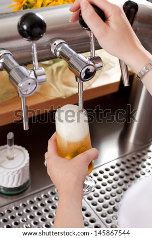 Refreshing frothy pint of draft beer being dispensed into a glass by a bartender from a metal spigot in the keg behind the counter - stock photo