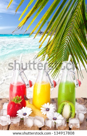 refreshing fruit cocktails with ice and fresh fruits on wooden table at a tropical beach