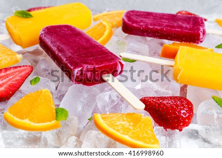 refreshing fruit popsicle lollies on ice background with berries, peppermint. - stock photo