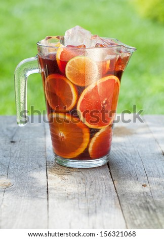 Refreshing fruit sangria (punch) on wood table - stock photo