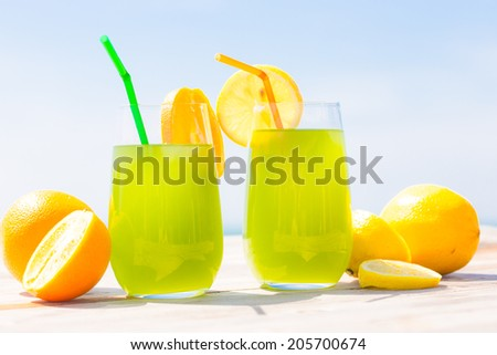 Refreshing fruity juice with the fresh lemon and orange on the wood with sea scenery - stock photo