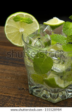 refreshing gin tonic on the wooden table on black background - stock photo
