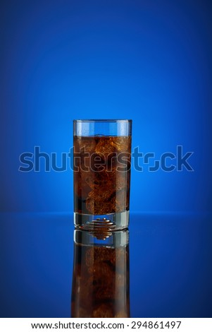Refreshing glass cola soft drink on a blue background. Cool liquid drink cola into a cold glass with ice. Beverage for promoting restaurant and bar. Closeup isolated design brown liquor sparkling.