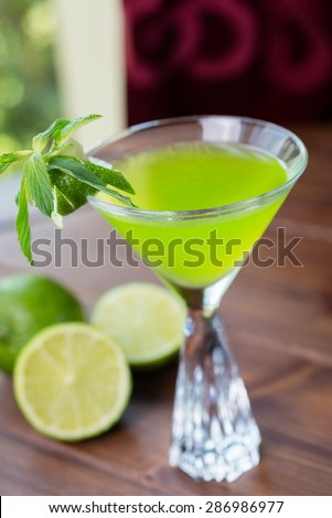 refreshing glass of cold apple lemonade with mint and ice on a wooden table in a restaurant with a creative decoration of mint leaves and fresh apples. soft focus