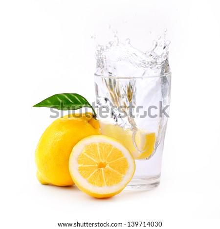 refreshing glass of water with splashed lemon isolated on white - stock photo