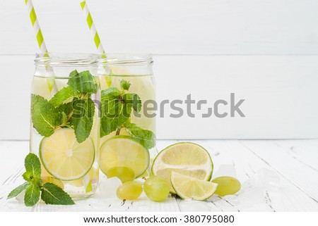 Refreshing homemade lime and mint cocktail over old vintage wooden table. Detox fruit infused flavored water. Clean eating. Copy space background - stock photo